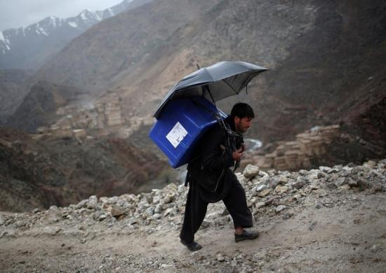 Afghani man backpacking a ballot box up a mountainous trail in the rain