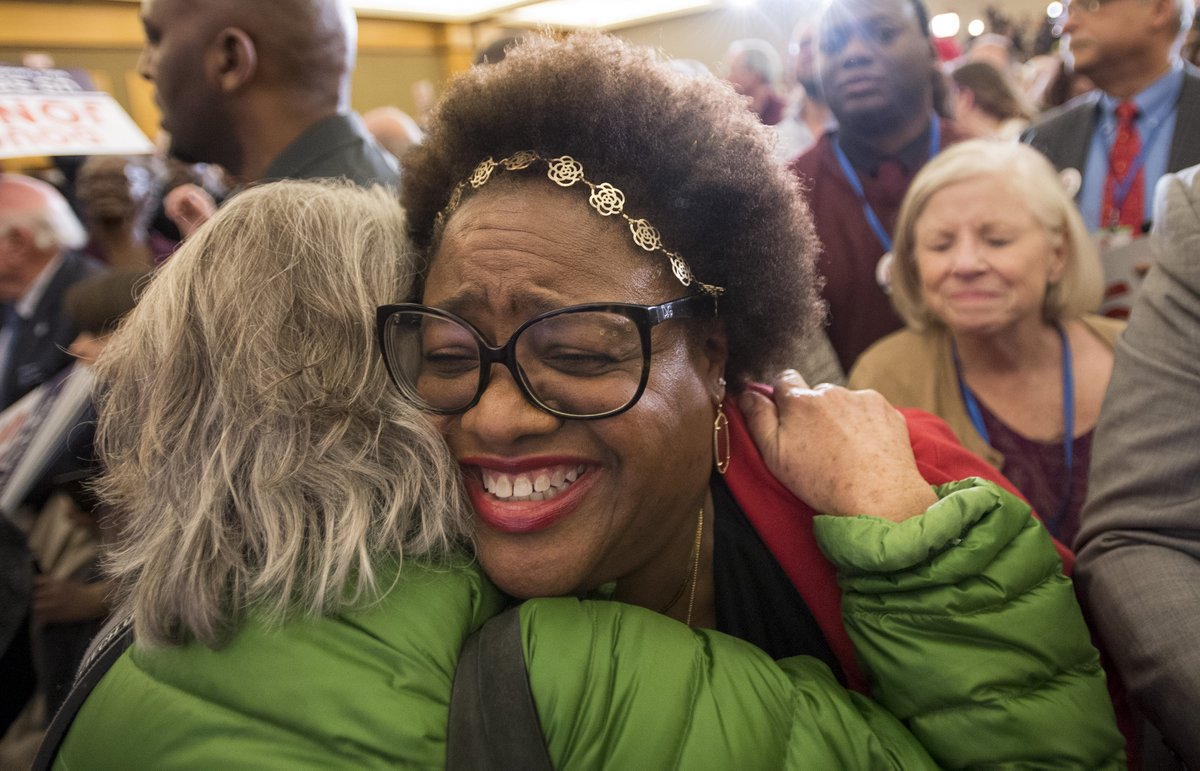black woman hugging white woman in a crowd