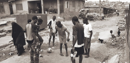 Group of boys playing on a grubby slum street. They and the photographer are oblivious to the woman passing within a few inches of them, a black-shrouded ghost