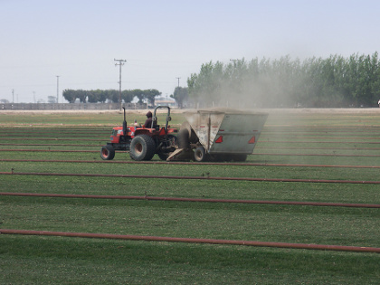 tractor using fuel to vacuum grass clippings on a sod farm